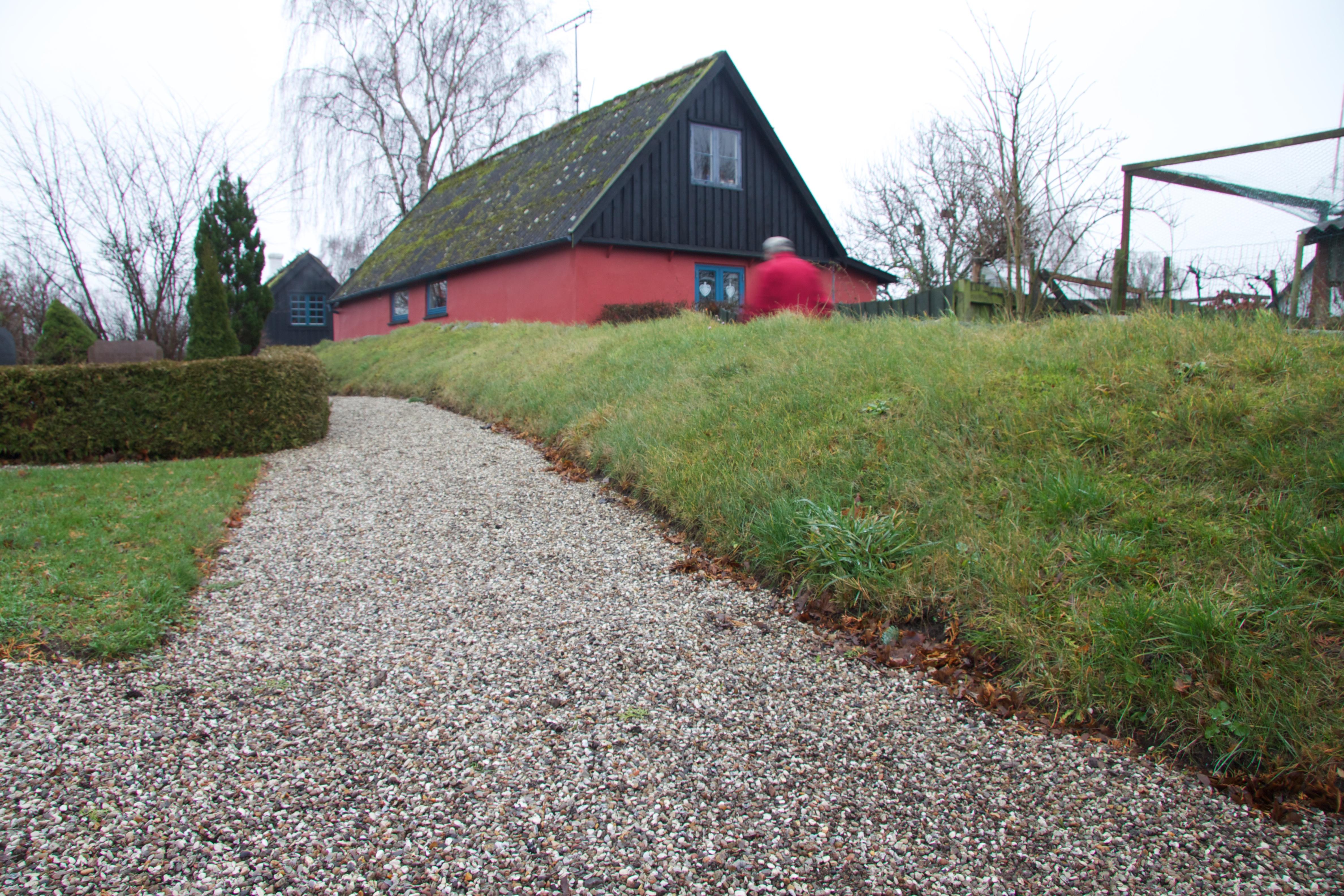 Til højre for kirkegårdens indgang løber dette græsbevoksede jorddige i skel mod landsbyen.