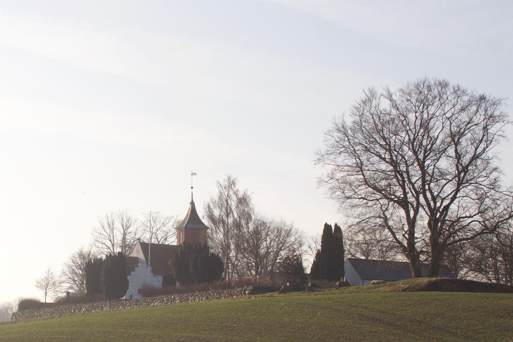 Kornerup Kirke og kirkegård set fra øst, hvor et iøjnefaldende stendige danner en flot ramme om den lille kirke og kirkegård i det store landskab.